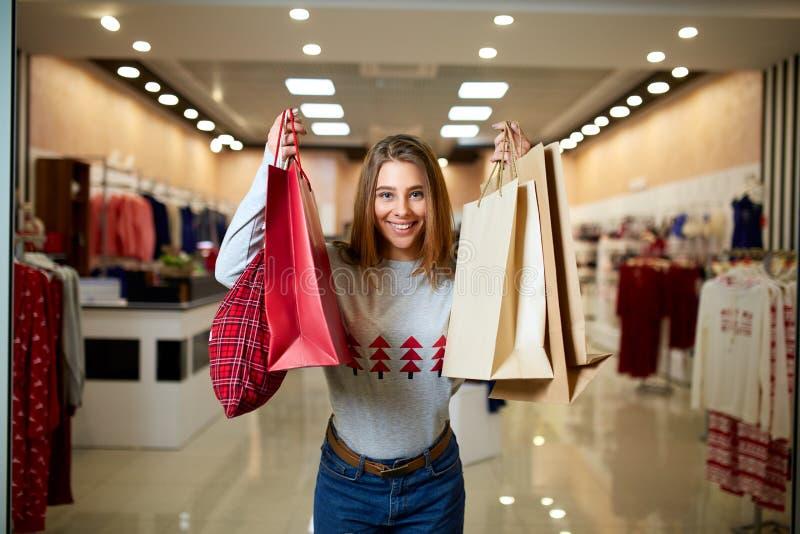 Lyckliga flickashoppinggåvor i galleria på julförsäljning Det nya året semestrar shoppa idébegrepp le kvinna royaltyfria foton