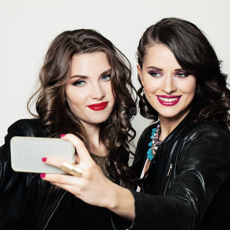 Lyckliga flickavänner med att le för mobiltelefon arkivfoton