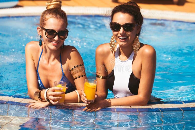 Lyckliga flickavänner med drinkar vid pölen royaltyfri foto