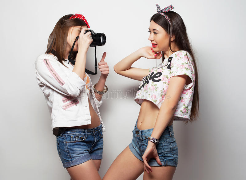 Lyckliga flickavänner som tar några bilder med kameran, över vit bakgrund royaltyfri foto
