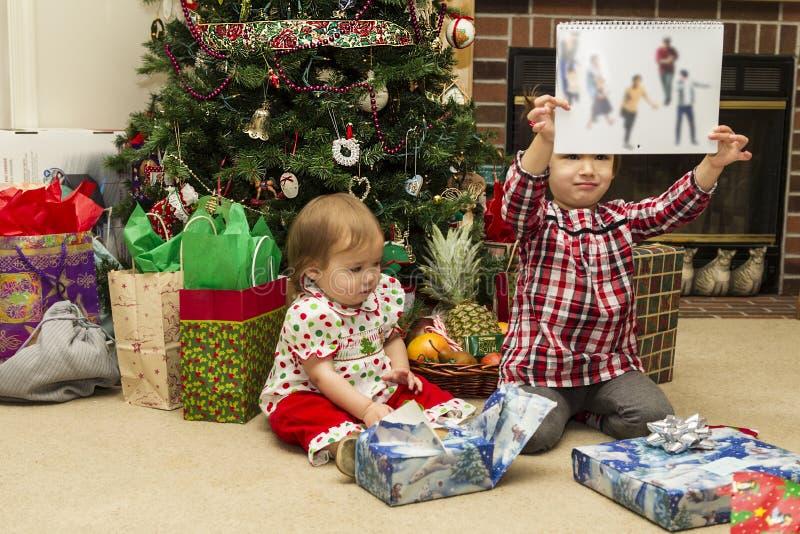 Lyckliga flickor öppnar julgåvor arkivfoto