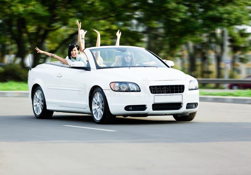 Lyckliga flickor i cabrioleten med utsträckta armar arkivfoto