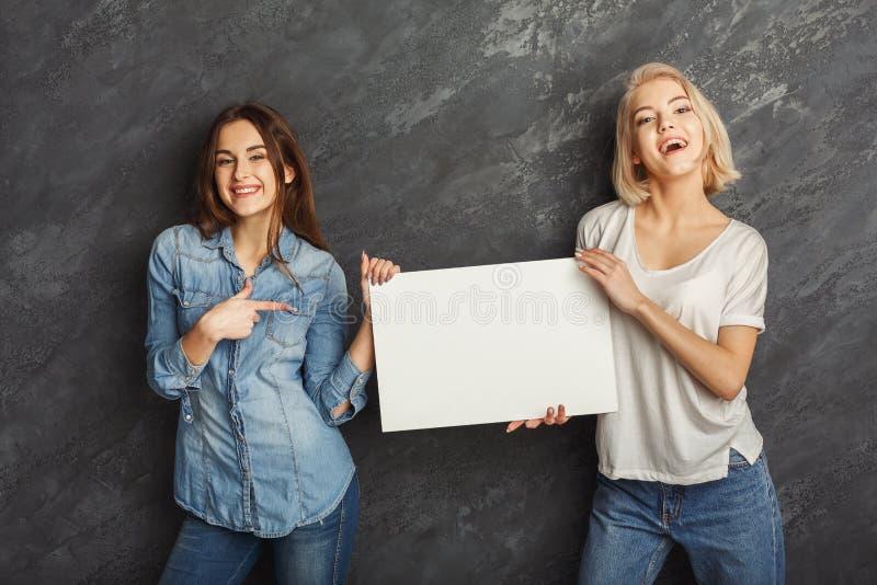 Lyckliga flickor med det tomma vita banret på mörk studiobakgrund arkivfoto