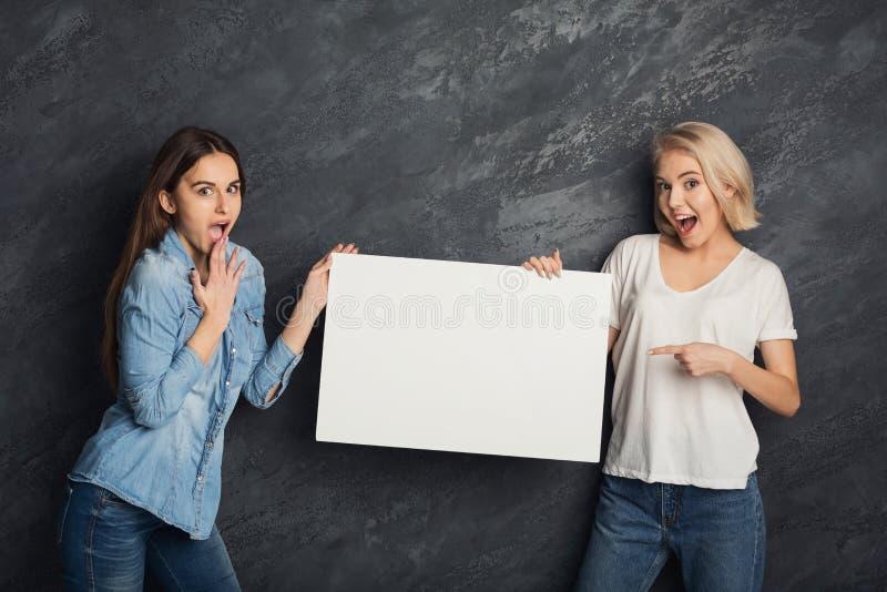 Lyckliga flickor med det tomma vita banret på mörk studiobakgrund arkivbild