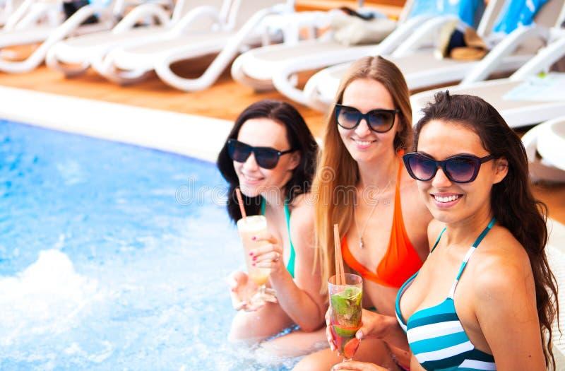 Lyckliga flickor med drycker på sommar festar nära pölen, sommar royaltyfri bild