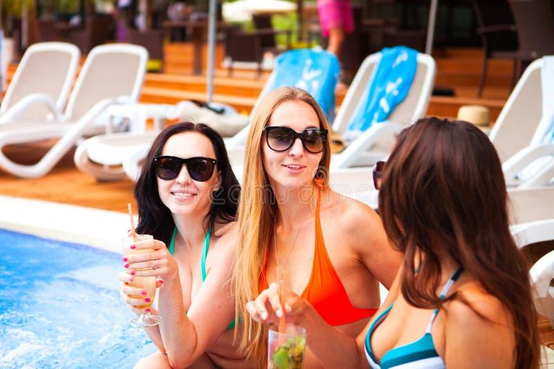 Lyckliga flickor med drycker på sommar festar nära pölen, sommar fotografering för bildbyråer