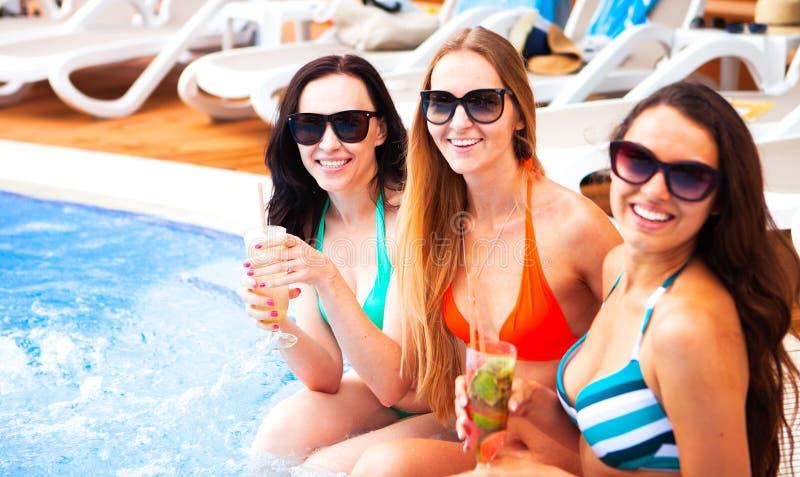 Lyckliga flickor med drycker på sommar festar nära pölen, sommar arkivbilder