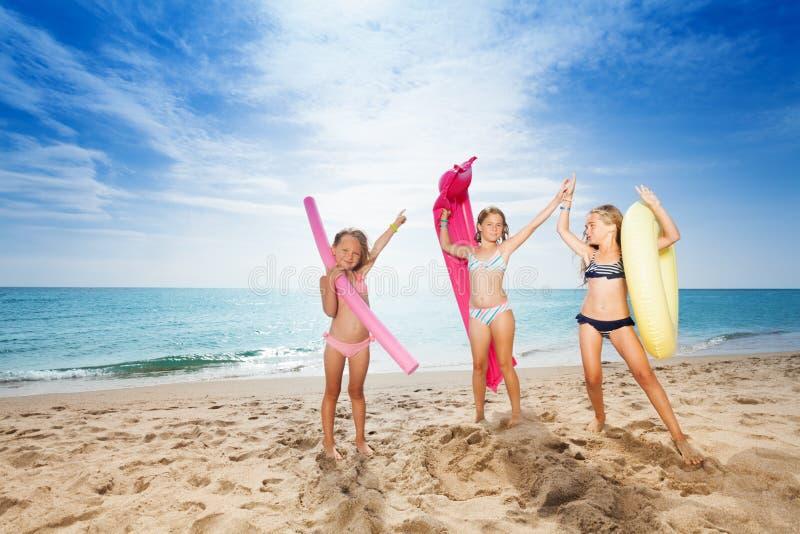Lyckliga flickor med simninghjälpmedel på den sandiga stranden arkivfoton