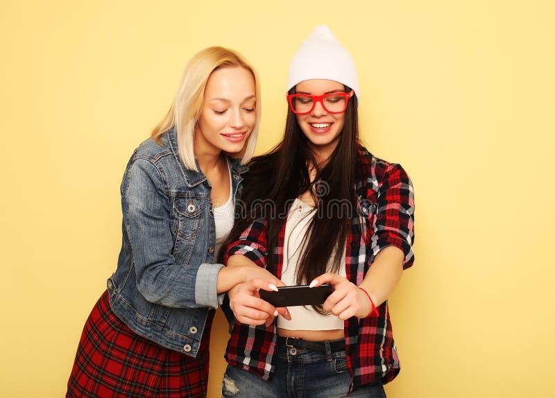 Lyckliga flickor med smartphonen över gul bakgrund Lycklig själv arkivfoto