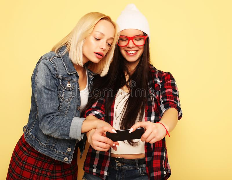 Lyckliga flickor med smartphonen över gul bakgrund Lycklig själv arkivfoton