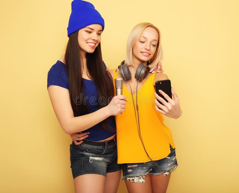 Lyckliga flickor med smartphonen över gul bakgrund Lycklig själv arkivbild