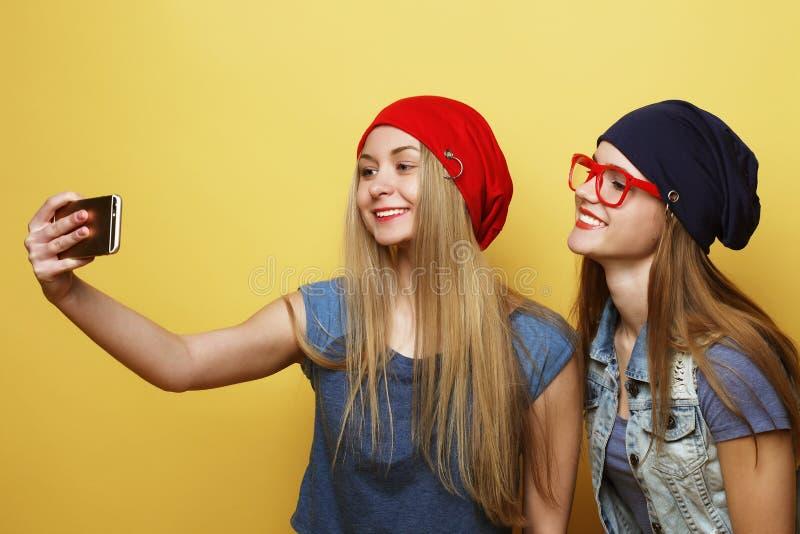 Lyckliga flickor med smartphonen över gul bakgrund Lycklig själv royaltyfria bilder