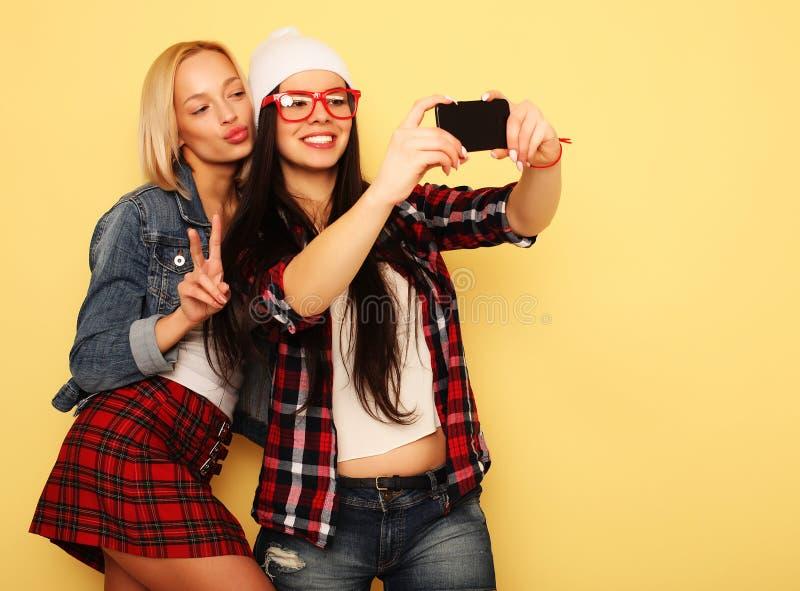 Lyckliga flickor med smartphonen över gul bakgrund Lycklig själv fotografering för bildbyråer