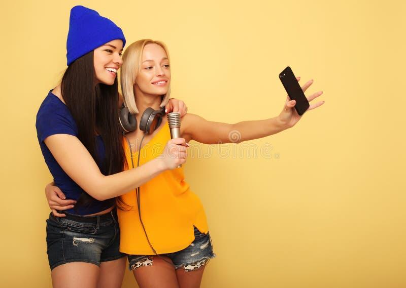 Lyckliga flickor med smartphonen över gul bakgrund Lycklig själv arkivbilder