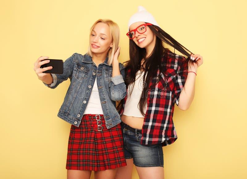 Lyckliga flickor med smartphonen över gul bakgrund Lycklig själv royaltyfri foto