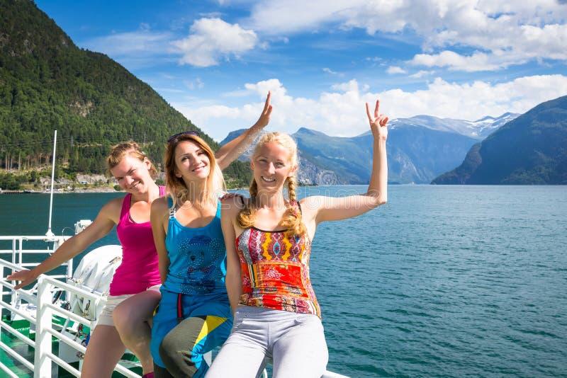 Lyckliga flickor på fjorden vänner tycker om bra väder i Norge royaltyfri bild
