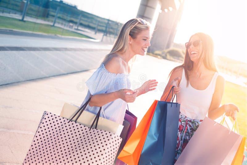 Lyckliga flickor på soligt med shoppingpåsar arkivfoton
