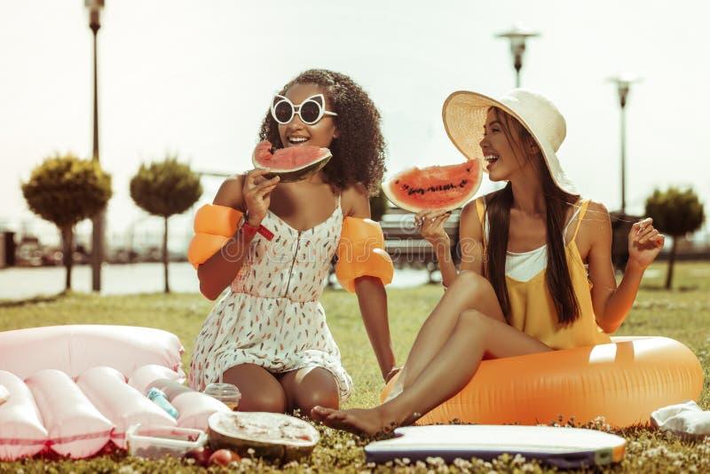 Lyckliga flickor som har en konversation och rymmer vattenmelon i händer royaltyfria foton