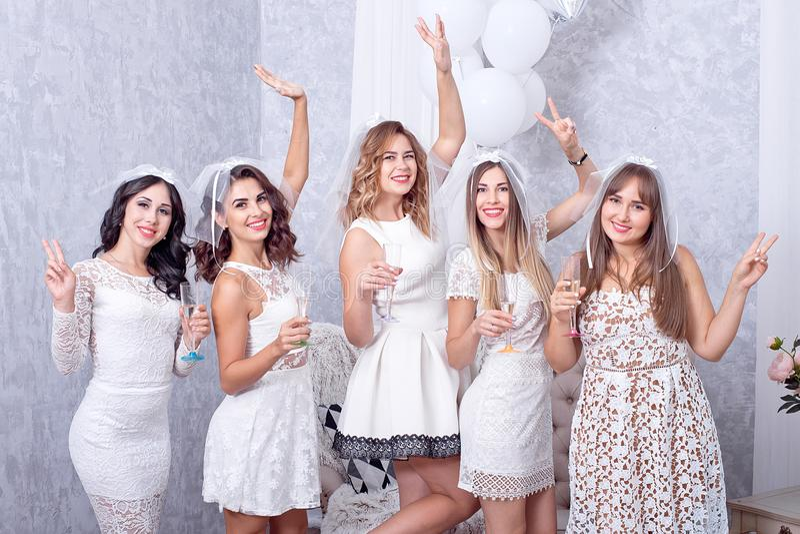 Lyckliga flickor som har gyckel som dricker champagne, möhippa arkivbilder