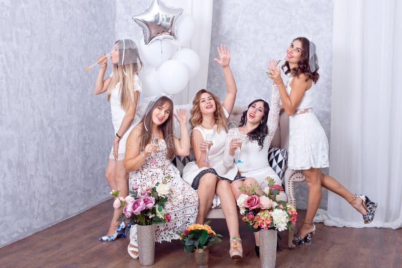 Lyckliga flickor som har gyckel som dricker champagne, möhippa royaltyfria foton