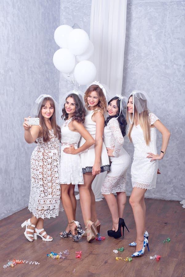 Lyckliga flickor som har gyckel som dricker champagne, möhippa royaltyfri fotografi