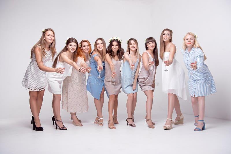Lyckliga flickor som har gyckel som dricker med champagne på partiet Begrepp av uteliv, ungmöparti, möhippa arkivbild