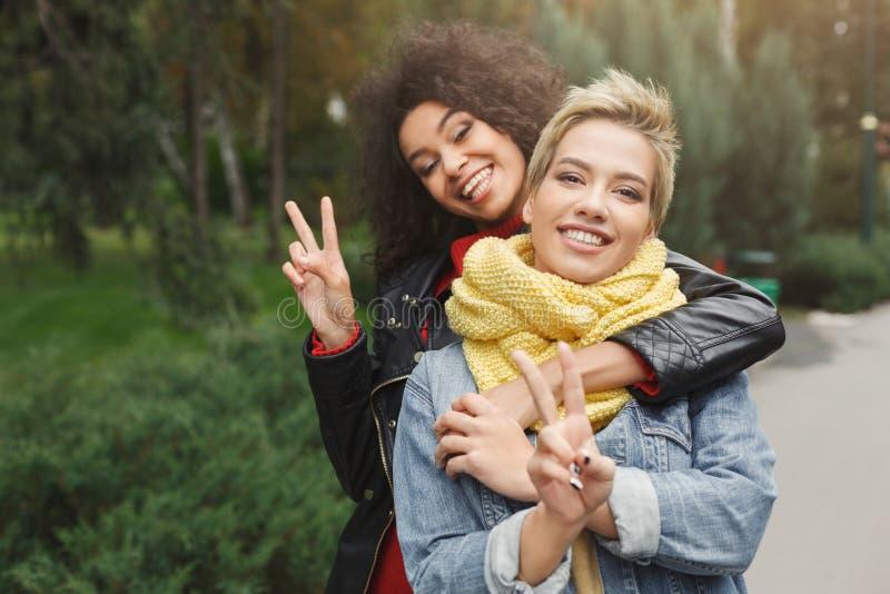 Lyckliga flickor som har gyckel, medan gå i parkera royaltyfri fotografi