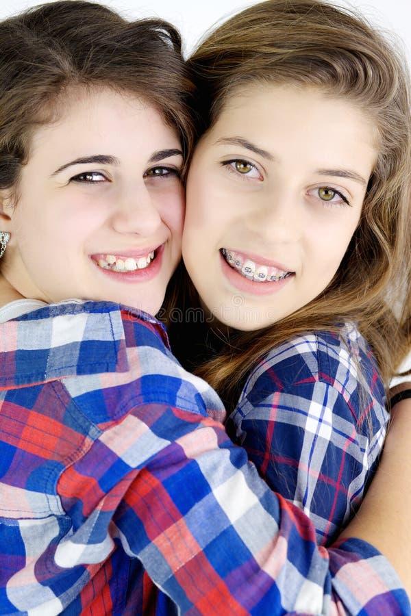 Lyckliga flickor som kramar att le i studio fotografering för bildbyråer