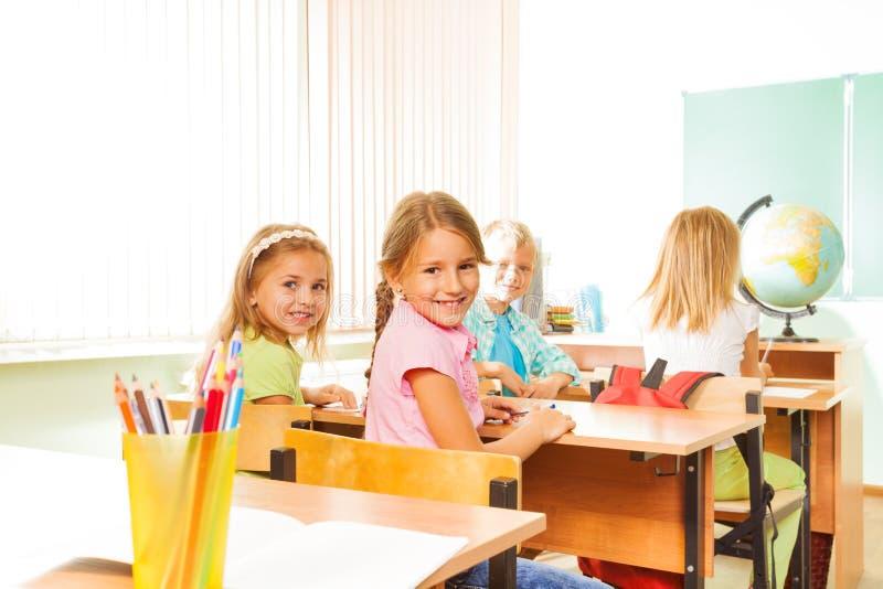 Lyckliga flickor som ser och sitter i rader på skrivbord royaltyfria bilder