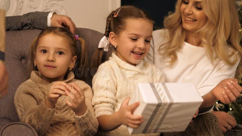 Lyckliga flickor som skakar en gåva för att gissa vad är inre royaltyfri fotografi