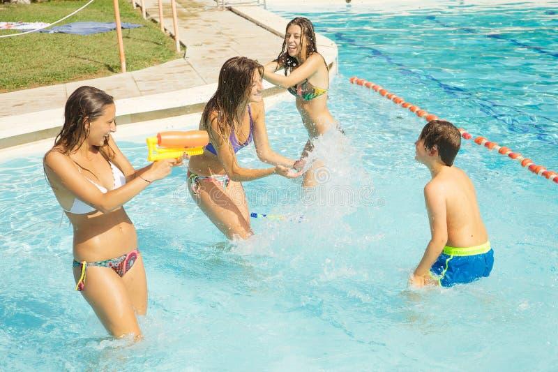 Lyckliga flickor som spelar med ungen i pöl med plaskande vatten för vattenvapen royaltyfri bild