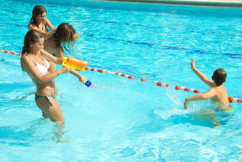 Lyckliga flickor som spelar med ungen i pöl med vattenvapnet royaltyfri bild
