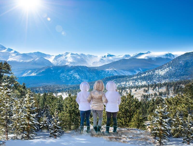 Lyckliga flickor som tycker om härlig vinterbergsikt royaltyfri foto