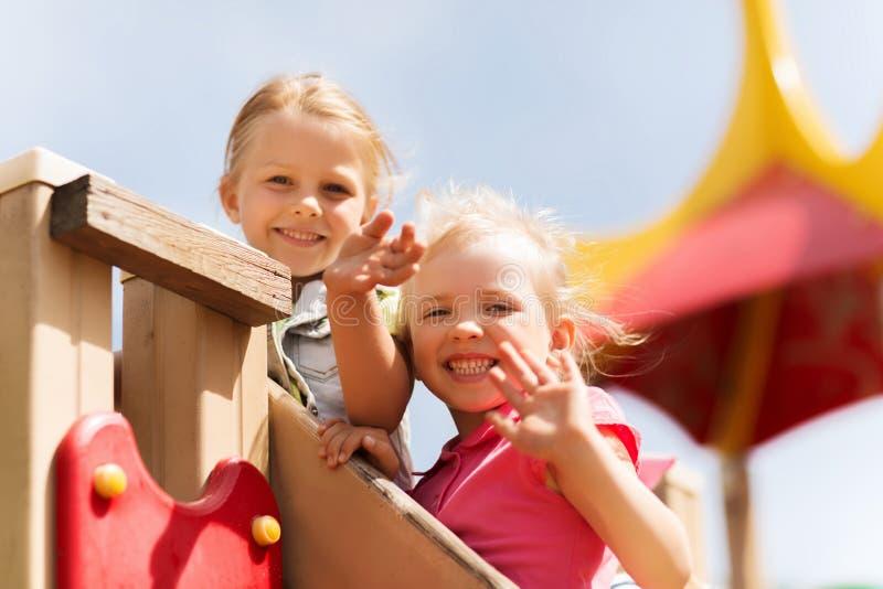 Lyckliga flickor som vinkar händer på barnlekplats arkivbilder