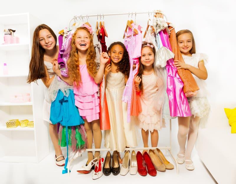 Lyckliga flickor under shopping som väljer kläder royaltyfri bild