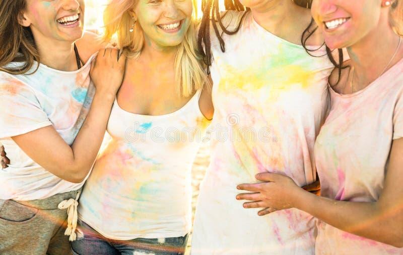 Lyckliga flickvänner som har gyckel på strandpartiet på holifestival fotografering för bildbyråer