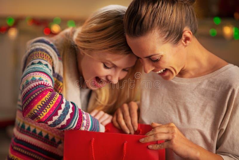 Lyckliga flickvänner som ser i shoppingpåse arkivbilder