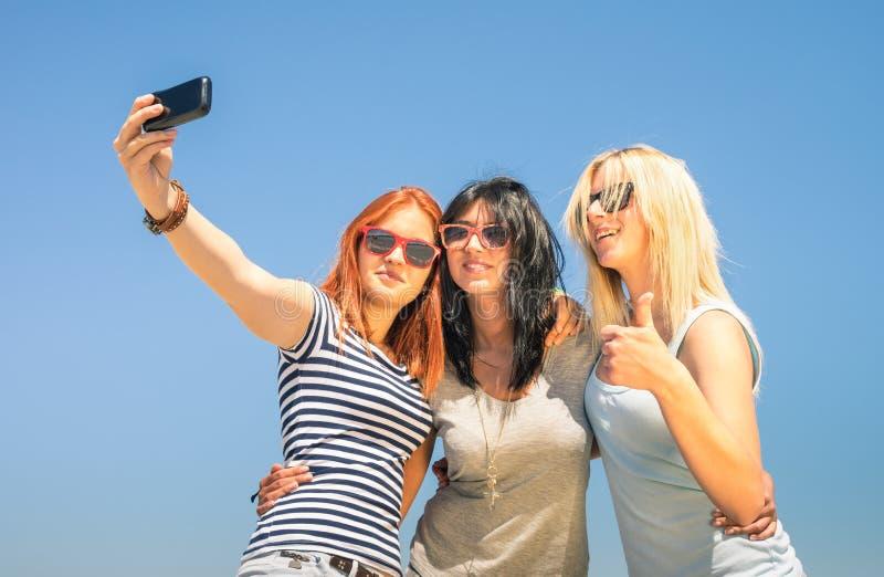 Lyckliga flickvänner som tar selfie mot blå himmel royaltyfri foto