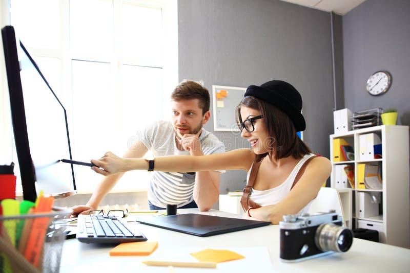 Lyckliga formgivare som arbetar på ett dokument med att arbeta för kollegor fotografering för bildbyråer