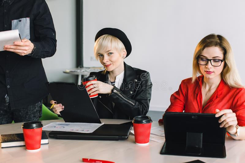 Lyckliga formgivare som tillsammans arbetar i deras kontor Två ung flickacoworkers som sitter på tabellen och arbetar under fotografering för bildbyråer