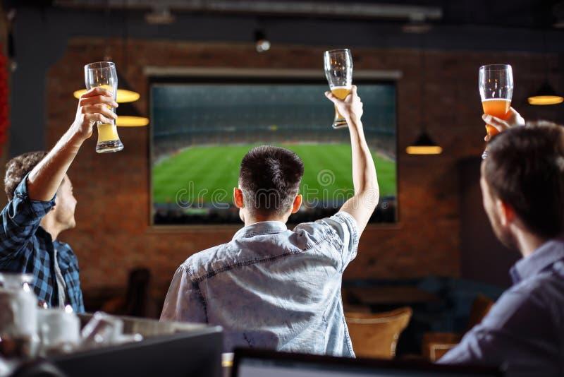 Lyckliga fotbollfans Tre vänner som håller ögonen på en lek på baren royaltyfri fotografi