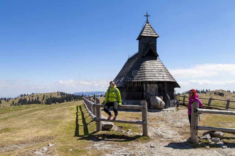 Lyckliga fotvandrare som vilar nära det lilla berget, kyrktar i bergnatur på solig dag royaltyfri bild