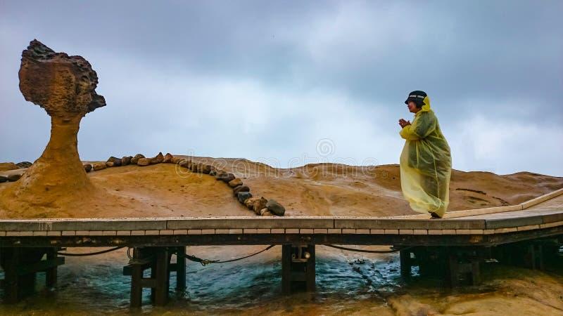 Lyckliga gamla asiatiska kvinnor bär en regnroat och lopp i taipei Yehliu geopark i regnig dag arkivfoto