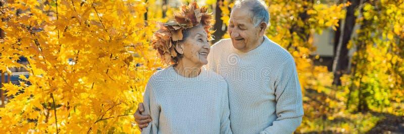 Lyckliga gamla par som har gyckel på hösten, parkerar Äldre man som bär en krans av höstsidor till hans äldre fruBANER arkivbild