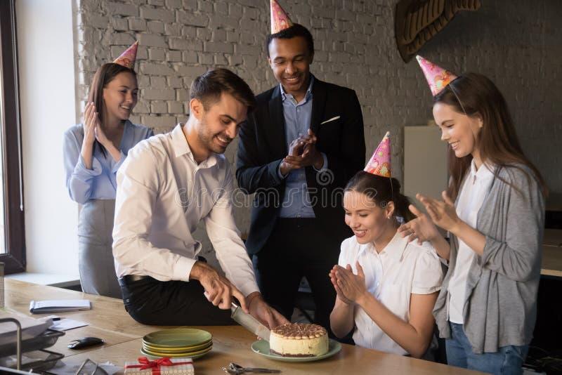 Lyckliga glade olika kollegor som firar födelsedag av jobbarkompisen royaltyfria foton