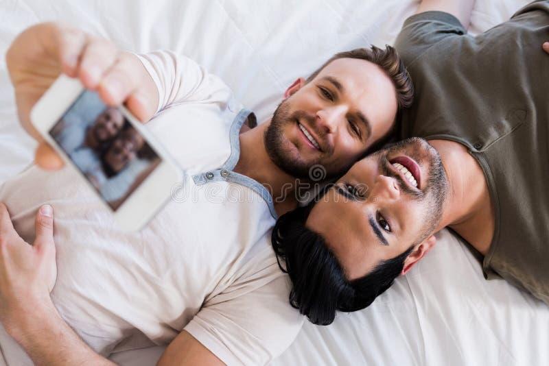 Lyckliga glade par som tar selfie på säng arkivbilder