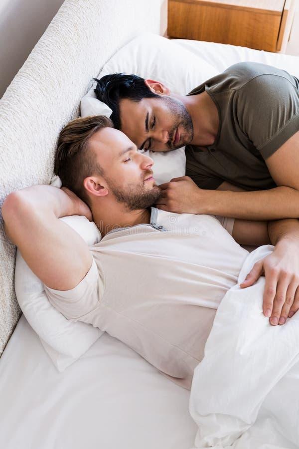 Lyckliga glade par som tillsammans sover på säng arkivbilder