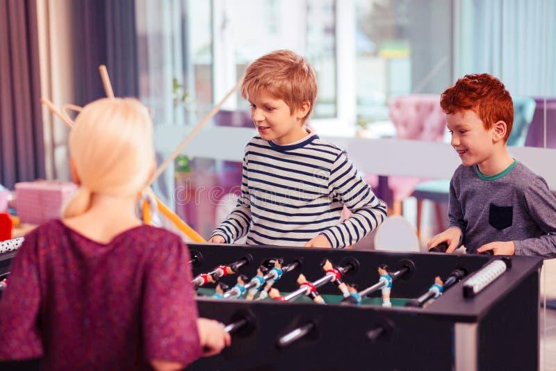 Lyckliga glade ungar som tillsammans spelar på partiet arkivbilder