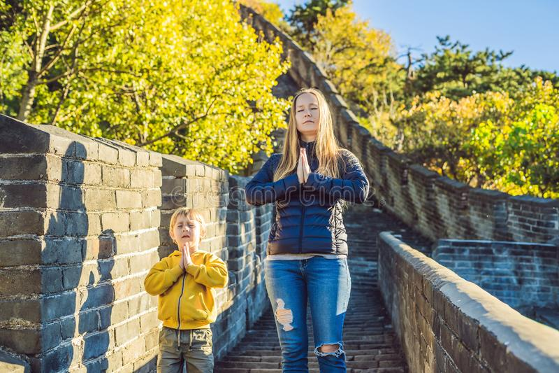 Lyckliga gladlynta glade turister mamma och son på den stora väggen av Kina mediterar på semestertur i Asien Kinesisk destination arkivbild