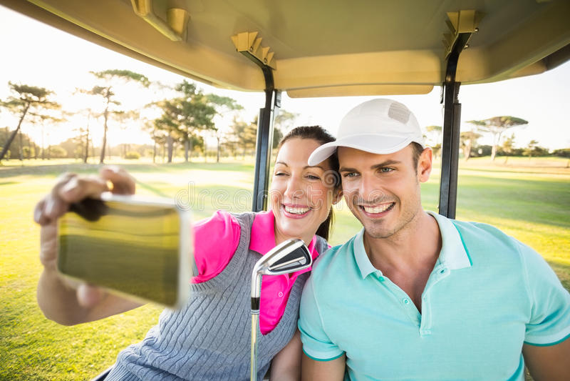 Lyckliga golfarepar som tar självståenden royaltyfri fotografi